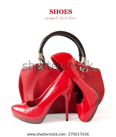 Red shoes pair and hand bag isolated on white background with sample text - stock photo