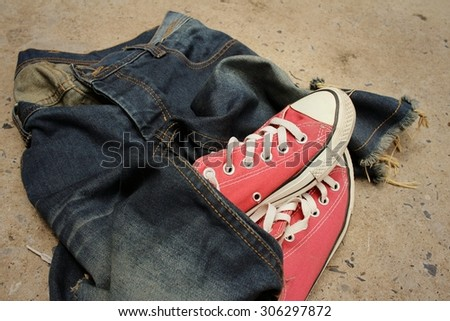 Red shoes with jeans on cement background.