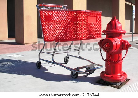 Red shopping cart parked next to a red fire hydrant