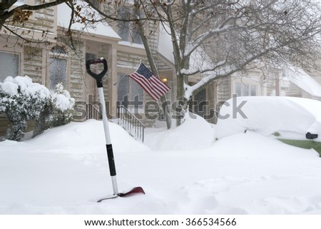 Red shovel and American flag waving during snow blizzard January 23 2016. Washington DC neighborhood area - stock photo