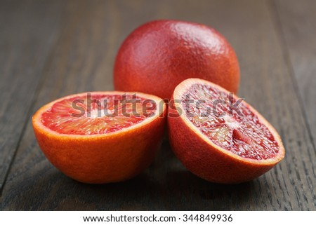 red sicilian oranges sliced on wooden table, vintage toned