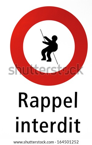 Red Sign saying mountaineering forbidden in this area on white background, the text is written in French. Rappel interdit. - stock photo