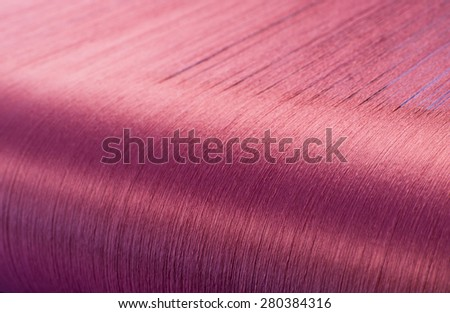 Red silk on a warping loom of a textile mill, Silk for weaving on a hand loom - stock photo