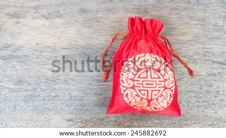 Red silky money bag on wood desk, Lucky Pouch Chinese tradition. - stock photo