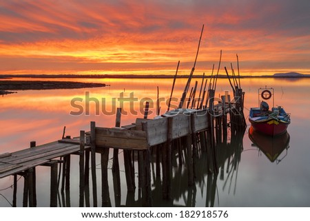 Red Sky Fire Sunset in the old port of artisanal fishing. The Carrasqueira Pier is a tourist destination in Alentejo, near Lisbon. - stock photo