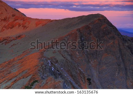 Red sky over the mountain peaks before dawn - stock photo