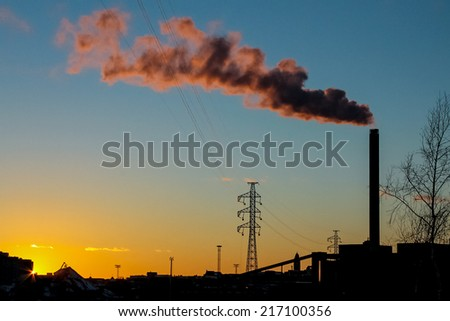 Red smoke coming from the power plant in the sunset