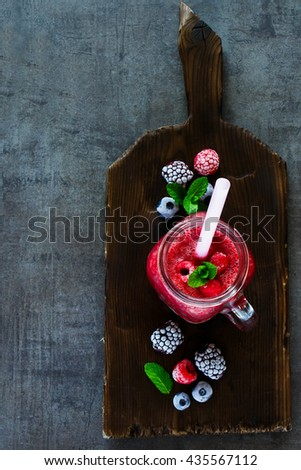Red smoothie drink in jar, served with fresh mint and frozen berries ingredients on dark chopping board over rustic background. Superfoods and health or detox diet food concept. - stock photo