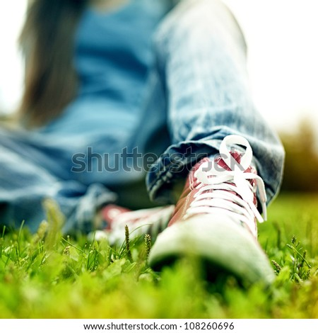 red sneakers on girl legs on grass during sunny serene summer day. - stock photo