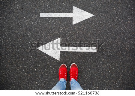 Red sneakers on the asphalt road with drawn arrows pointing to two directions. Making decisions and making choices
