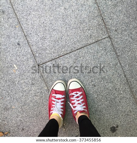 Red Sneakers Shoes Walking On Dirty Concrete Top View , Canvas Shoes Walking On Concrete Great For Any Use. - stock photo