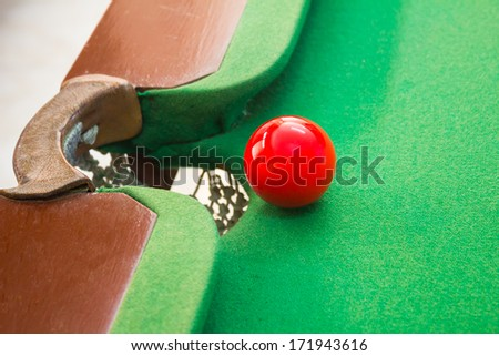 Red snooker ball near the middle hole on the table.