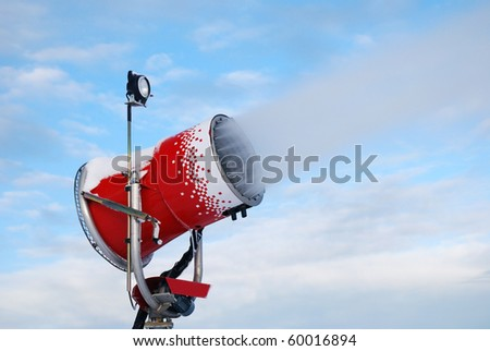 red snow cannon running under blue sky - stock photo