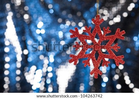 Red snow flake on a blue, silver glitter background for Christmas - stock photo