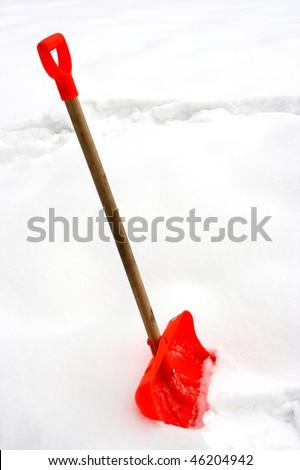 red snow shovel stick in snow-drift - stock photo