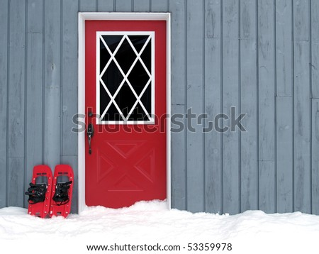 red snowshoes beside a red door in a paneled wall - stock photo