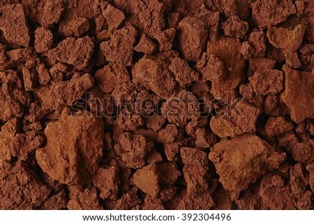 Red Soil Texture Background. Top View of a Rough Ground Surface. Close Up Macro View of Dirt and Stones. Text Space