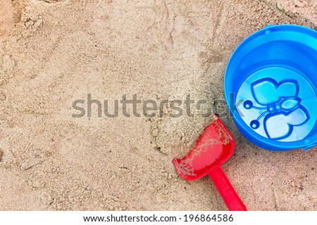 Red spade and blue bucket in the children's sandbox. View from above. - stock photo