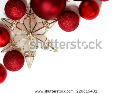 Red sparkly Christmas Bulb Decorations and a gold tree topper star are in the corner framing a white background for text, copyspace - stock photo