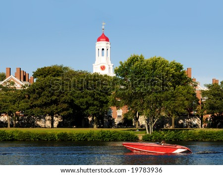 Red speed boat on Charles River passing by Harvard University Dunster House. - stock photo