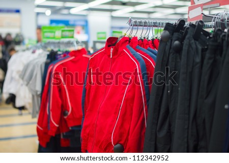 Red sport jackets and trousers on stands in supermarket - stock photo