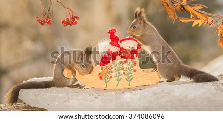 red squirrels with sled and santa on ice  - stock photo