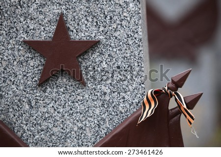 Red star and the Ribbon of Saint George at the Soviet War Memorial with graves of Soviet soldiers fallen in the last days of World War II at the Olsany Cemetery in Prague, Czech Republic. - stock photo