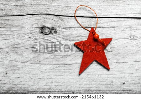 Red star Christmas decoration on grungy weathered textured wood with copyspace for your seasonal greeting - stock photo