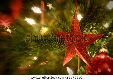 Red star ornament hanging on holiday or Christmas tree with lights blurred in the background.