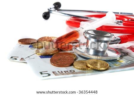 Red Stethoscope and a syringe with money - symbolizing expensive healthcare systems. Highkey image! - stock photo