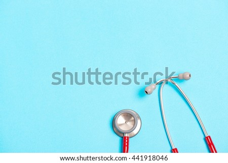 red stethoscope on blue background - stock photo