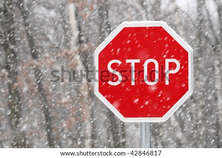 Red stop sign in winter snowy conditions - stock photo