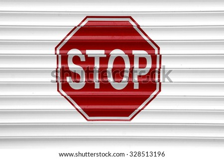 Red Stop Sign On The Automatic  Aluminum Roll-up White Garage Gate - stock photo