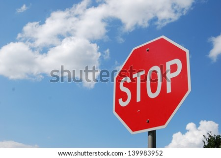 Red Stop Sign with Blue Sky and Clouds Background - stock photo
