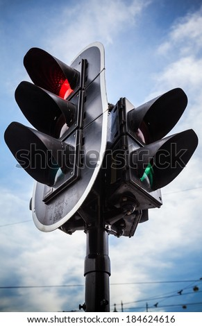 Red stop signal for cars and green pedestrian light on urban traffic light - stock photo