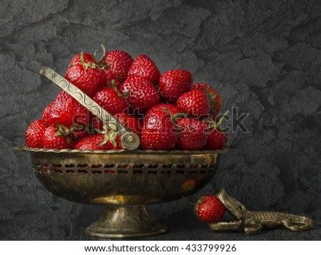 Red strawberries in vase.Fresh strawberries in new season.Strawberry fruits for sale. Summer strawberries in iron basket and an alligator eating the fruit.The garden strawberry on dark wood background - stock photo