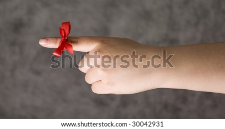 Red string around the finger as a reminder - stock photo