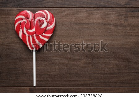 red sugar heart-shaped lollipop on the wooden table - stock photo