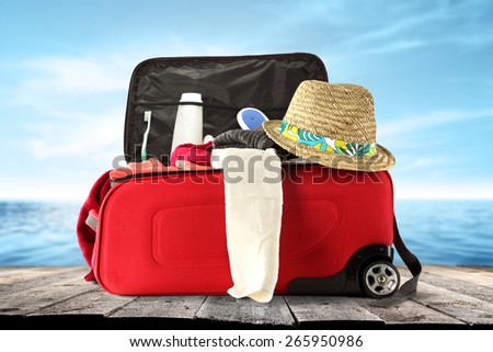 red suitcase hat and white towel  - stock photo