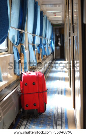 Red suitcase in corridor of  railway wagon