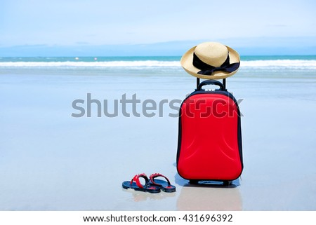 Red suitcase,red flip flop,woman hat with black ribbon on the beach, selective focus at suit case, travel concept - stock photo