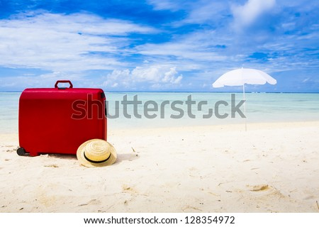 red suitcase, straw sun hat and white sunshade at a beach with a blue ky and some clouds - stock photo