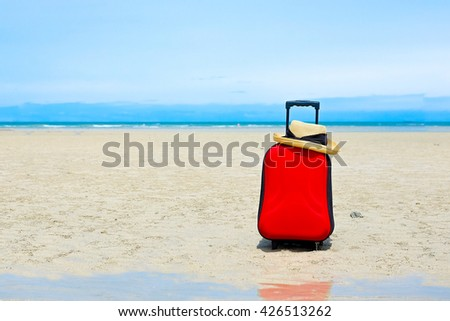 Red suitcase,woman hat with black ribbon on the beach, selective focus at suit case, travel concept - stock photo