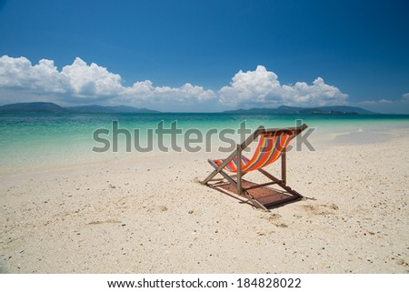 Red sun chair on the beach with the sea and blue sky background