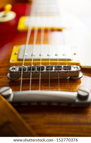 Red sunburst color single cutaway electric solid body guitar. Focus on bridge. Shallow depth of field.  - stock photo