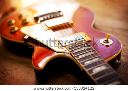 Red sunburst color single cutaway electric solid body guitar, on a old grungy wooden surface. Shallow depth of field. - stock photo