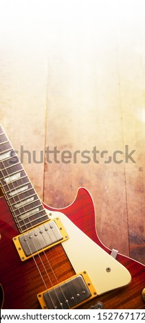 Red sunburst color single cutaway electric solid body guitar, on a old grungy wooden surface. fading in to white light.  - stock photo