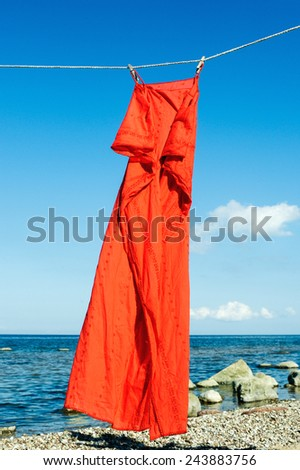 Red sundress hanging on a rope on the seashore - stock photo