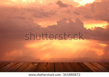 Red sunset over the city covered by clouds and wooden floor - stock photo