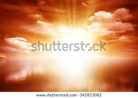 Red sunset over the sea, rich in dark clouds, rays of light. Reflection in water. - stock photo